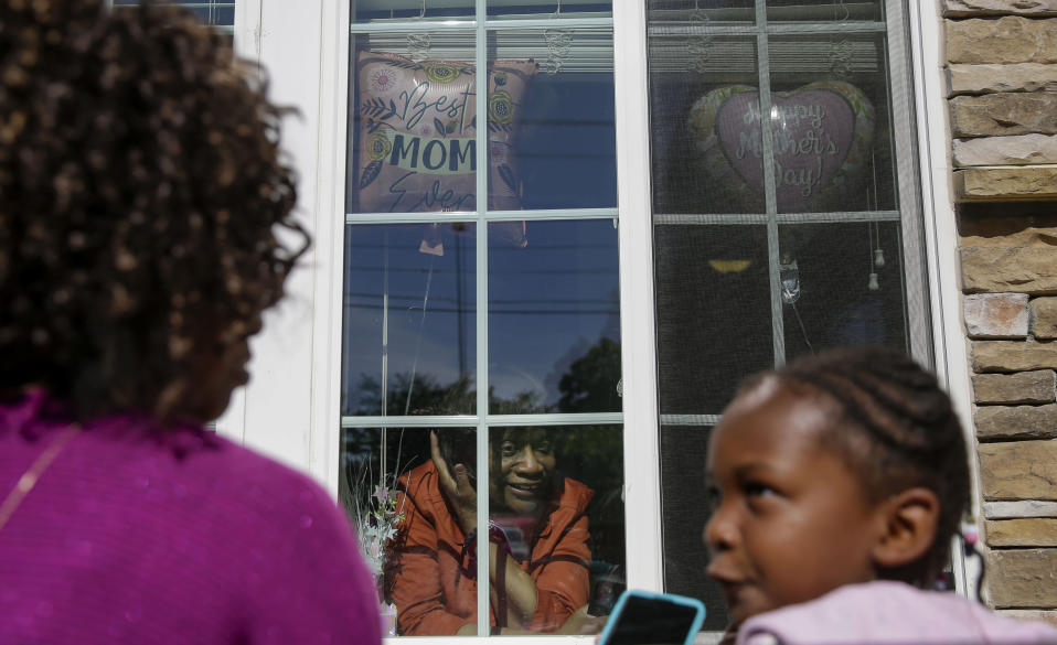 Mary Washington, 73, speaks through a window to her daughter, Courtney Crosby and grandchild Sydney Crosby for a Mother's Day celebration at Provident Village at Creekside senior living on Sunday, May 10, 2020, in Smyrna, Ga. (AP Photo/Brynn Anderson)