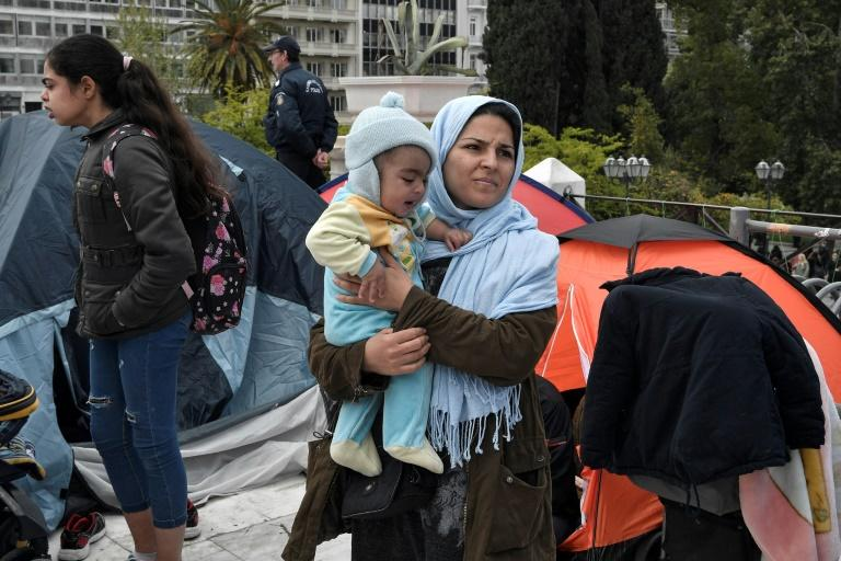A mother and a child stand among tents as a group of migrants and refugees camped out at the central Athens Syntagma following their eviction from a squatted building, claiming they have nowhere to go