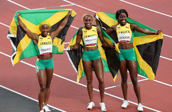 Jamaica's Shelly-Ann Fraser-Pryce, Jamaica's Elaine Thompson-Herah and Jamaica's Shericka Jackson pose for a group picture after the women's 100m final at the Tokyo 2020 Olympic Games.(Photo by GIUSEPPE CACACE/AFP via Getty Images)