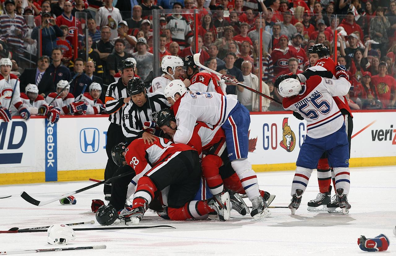 OTTAWA, CANADA - MAY 5: Linesman Jay Sharrers #57 and referee Paul Devorski #10 try to separate a fight between numerous players as Zack Smith #15 of the Ottawa Senators and Francis Bouillon #55 of the Montreal Canadiens fight off to the right in Game Three of the Eastern Conference Quarterfinals during the 2013 NHL Stanley Cup Playoffs at Scotiabank Place, on May 5, 2013 in Ottawa, Ontario, Canada.  (Photo by Jana Chytilova/Freestyle Photography/Getty Images)