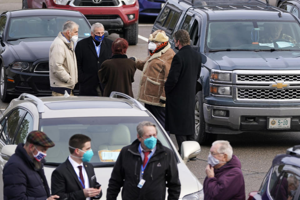 State Representatives gather prior to an outdoor meeting of the New Hampshire House of Representatives in a parking lot, due to the COVID-19 virus outbreak, at the University of New Hampshire Wednesday, Jan. 6, 2021, in Durham, N.H. (AP Photo/Charles Krupa)