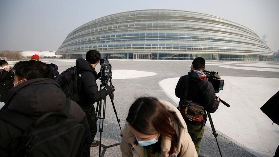 Media reporters are seen in front of the National Speed Skating Oval, a venue of the 2022 Winter Olympic Games, during an organised media tour in Beijing, China January 22, 2021.