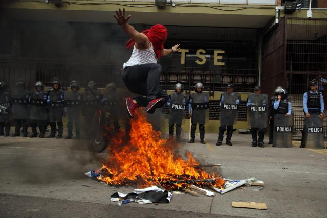 <p>A supporters of Libre Alliance presidential candidate Salvador Nasralla jumps over pyre of banners promoting Honduran President and current presidential Juan Orlando Hernandez in front of the Supreme Electoral Tribunal, during a protest claiming electoral fraud, in Tegucigalpa, Honduras, Wednesday, Nov. 29, 2017. (Photo: Fernando Antonio/AP) </p>
