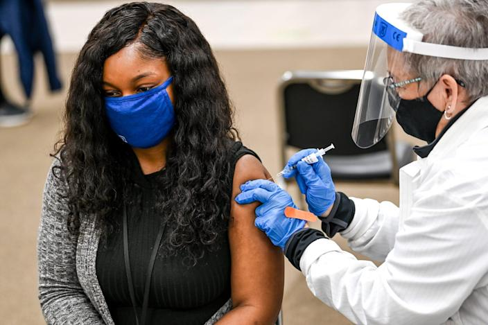 Constance Botke gives Micah Pierce of Lansing, Mich., her first COVID-19 vaccination shot on April 12 at Sparrow's COVID-19 vaccination site in Lansing.