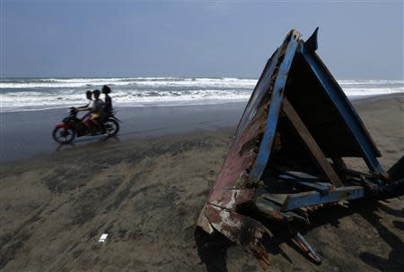 Children ride a motorcycle past a piece of wreckage of a boat which sank, at Agrabinta beach on the outskirts of Sukabumi