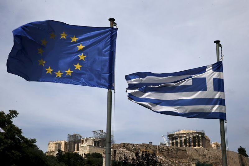 An EU flag and a Greek national flag flutter as the ancient Parthenon temple is seen in the background in Athens