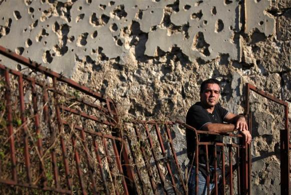 Zoran Laketa poses for a picture in front of a building destroyed during the 1992-1995 war in Bosnia, after an interview with Reuters, in Mostar April 2, 2012. Laketa epitomizes the complexities of the Bosnian conflict that kept the West dithering over intervention in the face of mass ethnic cleansing. Twenty years since the start of the war, ethnicity is still a deep dividing line - no more so than in Mostar, where Croats hold the west bank, Muslim Bosniaks the east, in an uncomfortable co-existence that has resisted foreign efforts to promote reintegration.