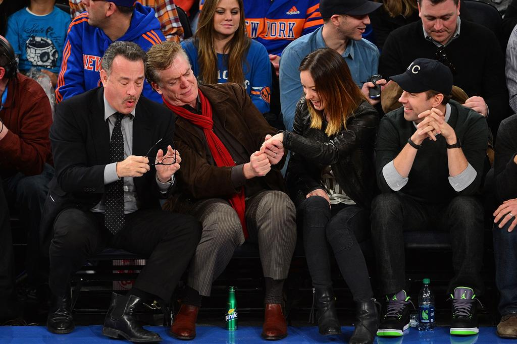 NEW YORK, NY - FEBRUARY 10:  Tom Hanks and Christopher McDonald look at Olivia Wilde's engagement ring with Jason Sudeikis while attending the Los Angeles Clippers vs New York Knicks game at Madison Square Garden on February 10, 2013 in New York City.  (Photo by James Devaney/WireImage)