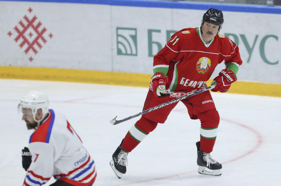 """FILE - In this March 28, 2020, file photo, Belarusian President Alexander Lukashenko, right, takes part in an ice hockey match during amateur competitions in Minsk, Belarus. Lukashenko presents a tough-guy image. At a spring 2020 hockey outing, he even dismissed the coronavirus by asking a TV reporter if she saw any viruses """"flying around"""" in the arena. (Andrei Pokumeiko/BelTA Pool Photo via AP, File)"""