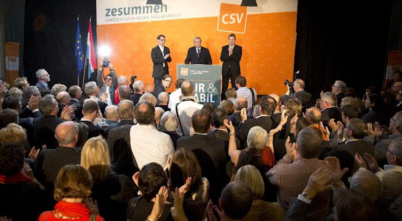 Leader of the Christian Democrat party Jean-Claude Juncker, center, receives applause from party members and supporters at his election headquarters in Luxembourg on Sunday, Oct. 20, 2013. The Christian Democrat party of long-serving Prime Minister Jean-Claude Juncker easily remained the biggest party and the first choice to form a new coalition government following the first provisional results of Sunday's elections. (AP Photo/Virginia Mayo)