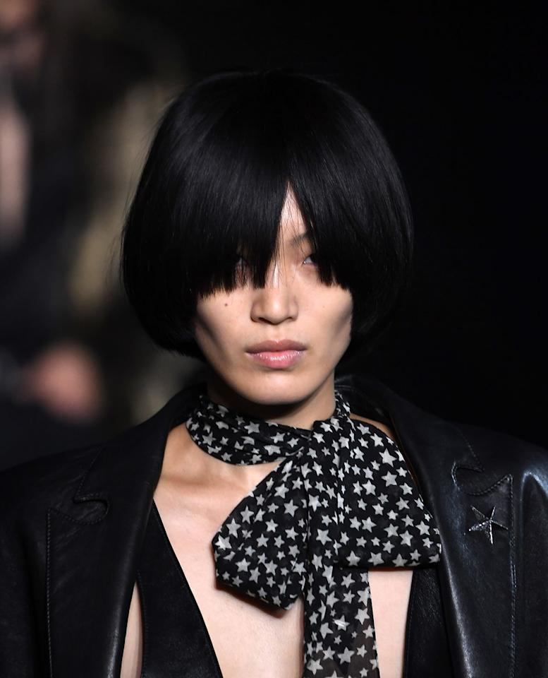 """<p>The bowl cut also made an appearance on Saint Laurent's Spring 2019 runway. Hairstylist <a href=""""https://www.instagram.com/duffy_duffy/"""" target=""""_blank"""">Duffy</a> gave the cut a rock n roll vibe by giving models long symmetrical bangs that hit just above the cheekbone and covered their eyes. </p>"""