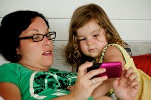 Kid being introduced to an iPhone