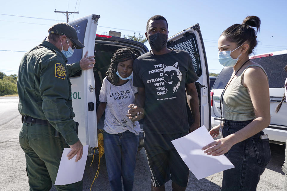 A U.S. Customs and Border Protection agent, left, drops off a migrant couple a member of of a humanitarian group, right, receives them after their release from custody, Friday, Sept. 24, 2021, in Del Rio, Texas. (AP Photo/Julio Cortez)