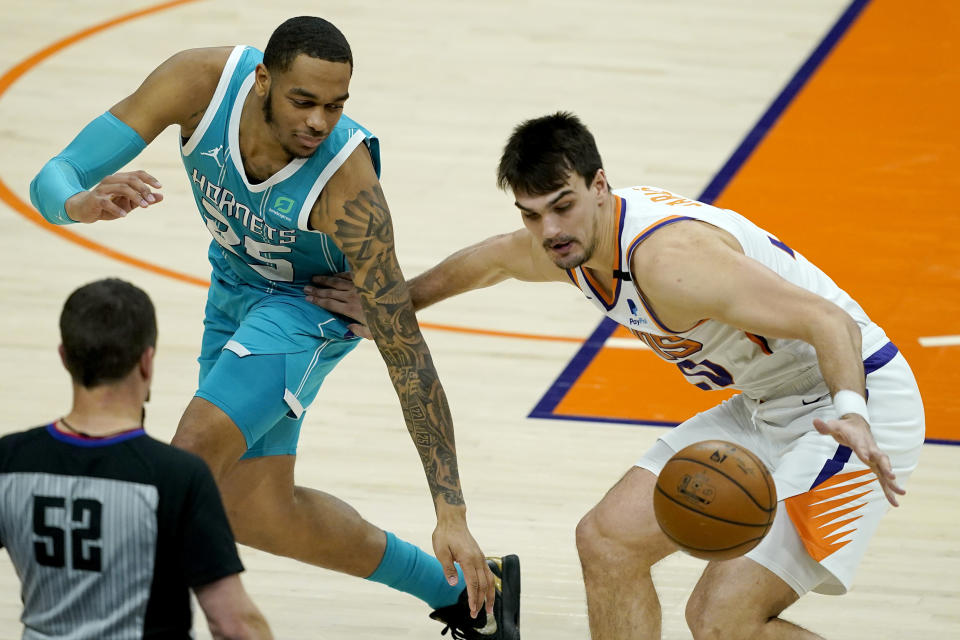 Phoenix Suns forward Frank Kaminsky, right, steals the ball from Charlotte Hornets forward P.J. Washington (25) during the first half of an NBA basketball game, Wednesday, Feb. 24, 2021, in Phoenix. (AP Photo/Matt York)