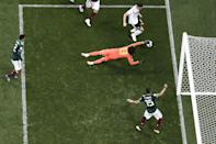 <p>Mexico's goalkeeper Guillermo Ochoa (C) dives to save a shot by Germany's forward Mario Gomez during the Russia 2018 World Cup Group F football match between Germany and Mexico at the Luzhniki Stadium in Moscow on June 17, 2018. (Photo by Mladen ANTONOV / AFP) </p>