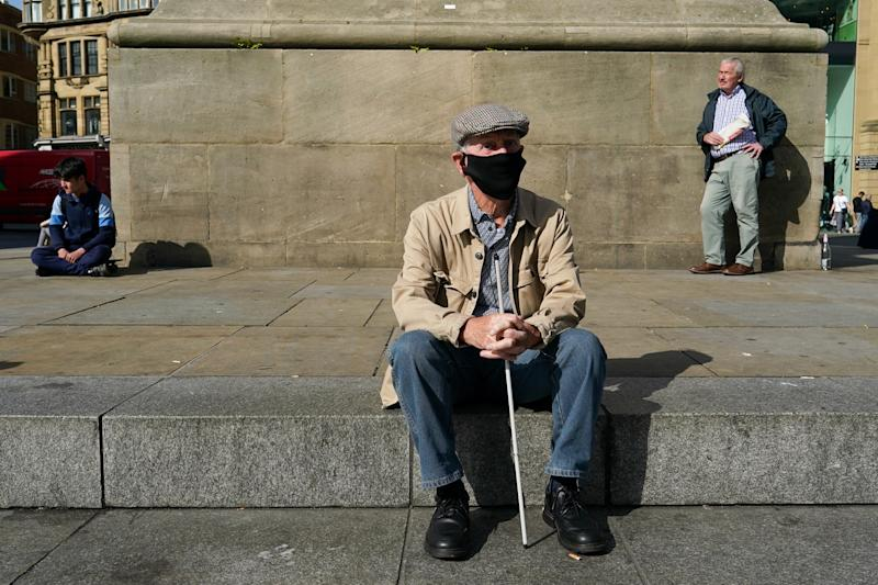 NEWCASTLE UPON TYNE, ENGLAND - SEPTEMBER 17: A man sits at the bottom of Grey's Monument in Newcastle on September 17, 2020 in Newcastle upon Tyne, England. Almost two million people in north-east England will be banned from mixing with other households and pubs will close early as coronavirus cases rise. Health Secretary Matt Hancock announced the temporary restrictions will be in place from midnight due to concerning rates of infection. The measures affect seven council areas, Newcastle, Northumberland, North Tyneside, South Tyneside, Gateshead, County Durham and Sunderland. (Photo by Ian Forsyth/Getty Images)