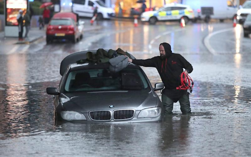 A man with car in a flooded street Sheffield - PA