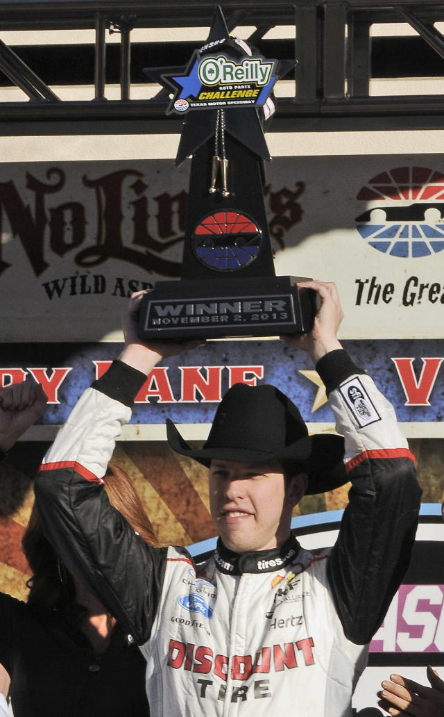 Brad Keselowski wears a cowboy hat and hoists the trophy after winning the NASCAR Nationwide Series auto race at Texas Motor Speedway in Fort Worth, Texas, Saturday, Nov. 2, 2013. (AP Photo/Larry Papke)