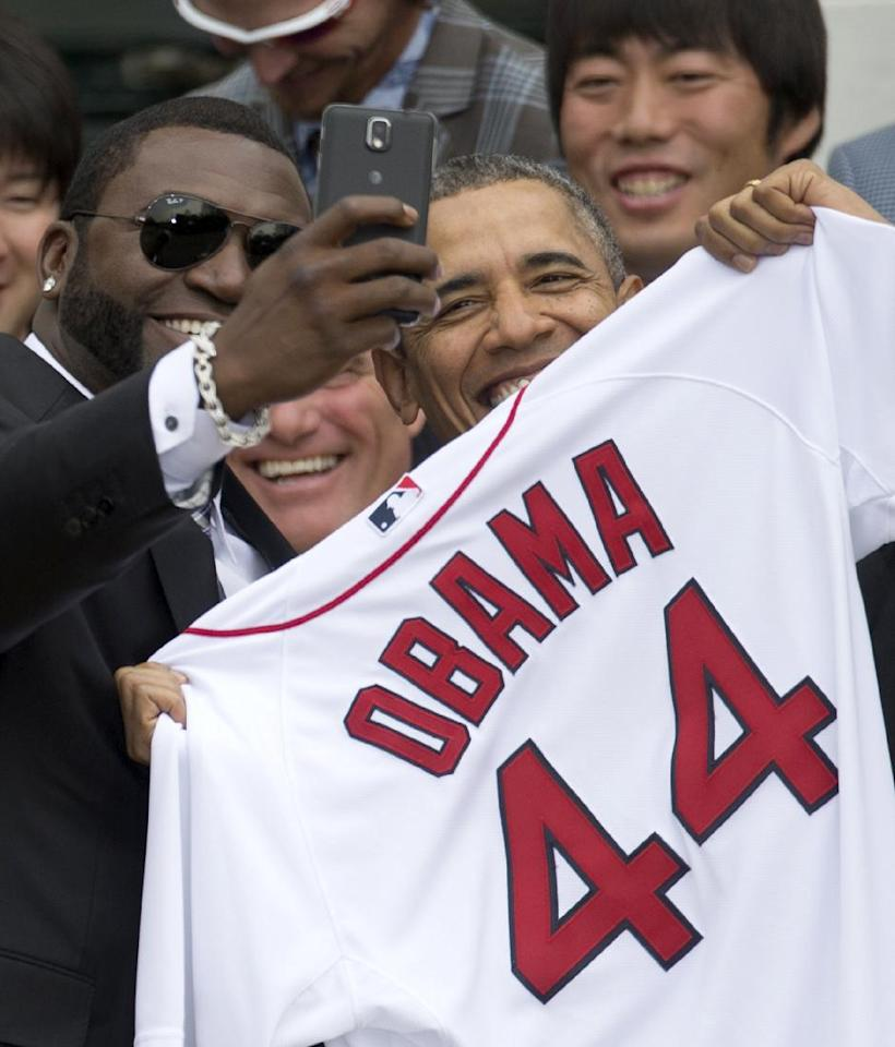 "Boston Red Sox designated hitter David ""Big Papi"" Ortiz takes a selfie with President Barack Obama, holding a Boston Red Sox jersey presented to him, during a ceremony on the South Lawn of the White House in Washington, Tuesday, April 1, 2014, where the president honored the 2013 World Series baseball champion Boston Red Sox. In the background is pitcher Koji Uehara, upper right. (AP Photo/Carolyn Kaster)"