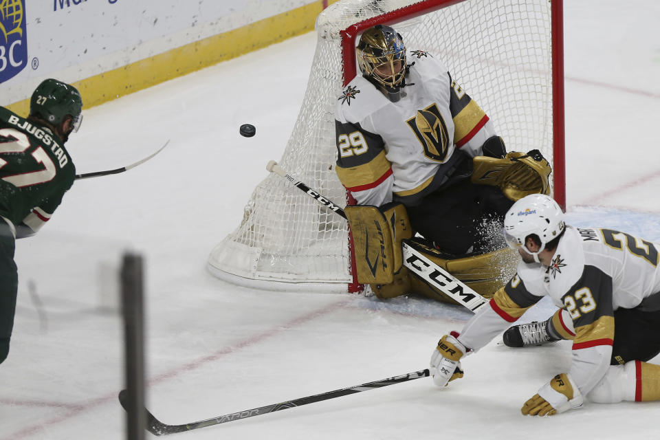 Vegas Golden Knights goalie Marc-Andre Fleury (29) blocks the puck with his body after Minnesota Wild's Nick Bjugstad (27) tried to make a goal in the third period of an NHL hockey game Monday, March 8, 2021, in St. Paul, Minn. (AP Photo/Stacy Bengs)