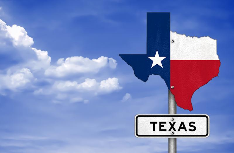 Texas-shaped sign with Lone Star flag coloring, in front of a blue sky with a few clouds.