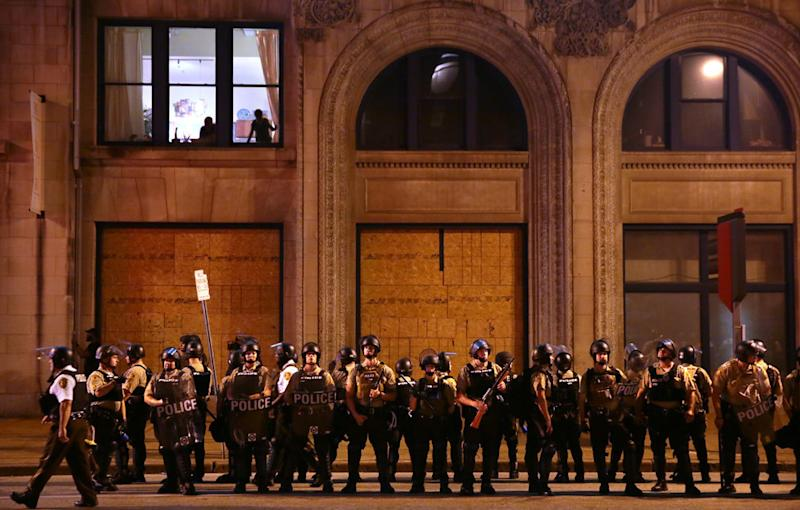 Residents watch as St. Louis County Police officers stand along Tucker Boulevard in downtown St. Louis as police order protesters to clear the area on Sunday, Sept. 17.<i></i>