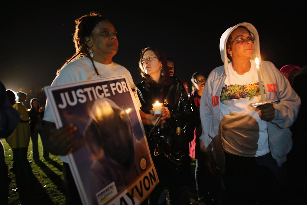 SANFORD, FL - FEBRUARY 26: Debra (who didn't want to use her last name), Julie Lambakis and Jeanette Holloway gather with others for a candle light vigil at Fort Mellon Park to mark the one year anniversary of when Trayvon Martin was killed on February 26, 2013 in Sanford, Florida. Martin was shot by George Zimmerman while Zimmerman was on neighborhood watch patrol in the gated community of The Retreat at Twin Lakes in Sanford, Florida.  (Photo by Joe Raedle/Getty Images)