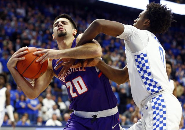 Evansville's Sam Cunliffe, left, is fouled by Kentucky's Ashton Hagans, right, late in the second half of an NCAA college basketball game in Lexington, Ky., Tuesday, Nov. 12, 2019. Cunliffe hit the two free throws. Evansville won 67-64. (AP Photo/James Crisp)