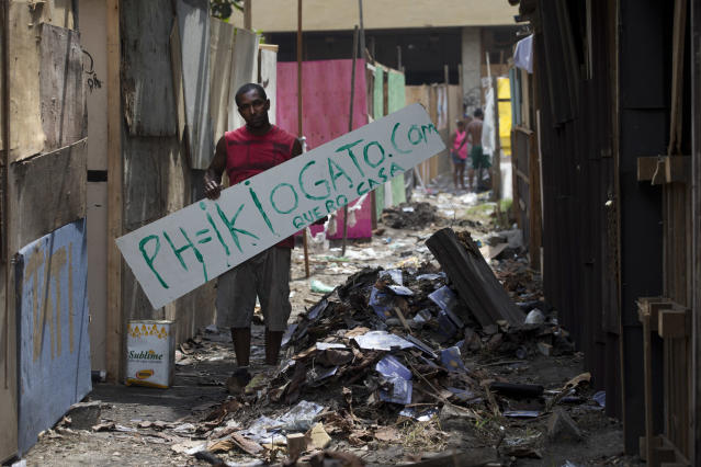 """Pedro Pereira holds a sign that reads in Portuguese; """"I want a house,"""" and the name of his blog, in an area recently occupied by squatters, in Rio de Janeiro, Brazil, Wednesday, April 9, 2014. Thousands of people have laid claim to a compound of abandoned office buildings owned by the private telecommunications company Oi, and named their settlement after the state-owned telecommunications Telerj. Authorities are negotiating with squatters to leave peacefully from the area they have occupied for more than a week.(AP Photo/Silvia Izquierdo)"""