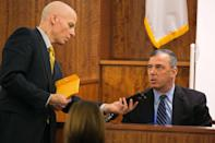District Attorney William McCauley (L) reviews the cell phone recovered from Odin Lloyd with North Attleboro Detective Michael Elliot during the murder trial for former NFL player Aaron Hernandez at the Bristol County Superior Court in Fall River, Massachusetts, February 17, 2015. REUTERS/Dominick Reuter (UNITED STATES - Tags: CRIME LAW)