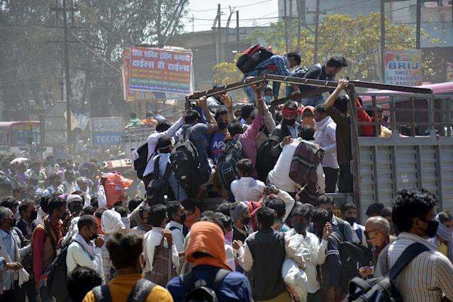 GHAZIABAD, INDIA - MARCH 28: Migrant workers try to board a goods truck bound to their native state during Day 4 of the 21 day nationwide lockdown -- to check the spread of coronavirus, at Lal Kuan bus stand, on March 28, 2020 in Ghaziabad, India. (Photo by Sakib Ali/Hindustan Times via Getty Images)