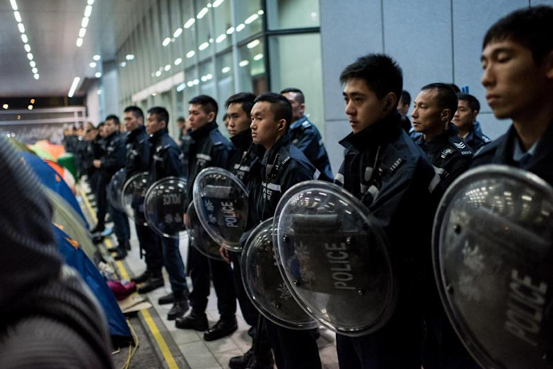 Police face pro-democracy democracy protesters on November 19, 2014 outside the central government offices in the Admiralty district of Hong Kong (AFP Photo/Alex Ogle)