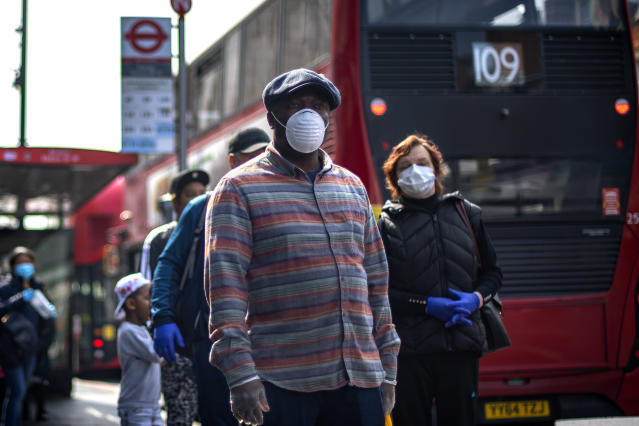 People wearing protective face masks wait in line for a supermarket in Brixton, South London, as the UK continues in lockdown to help curb the spread of the coronavirus.