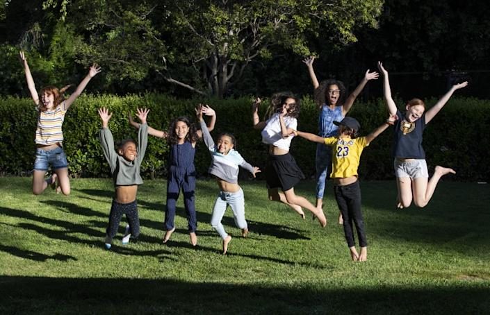 "The students of ""Brothbush Academy"" cheer for their home school on the Roths' front lawn in the midst of the coronavirus outbreak in Riverside. <span class=""copyright"">(Gina Ferazzi / Los Angeles Times)</span>"