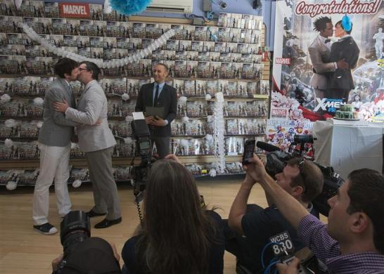 Friends and media photograph Jason Welker (L) and Scott Everhart as they kiss during their wedding ceremony at a comic book retail shop in Manhattan, New York June 20, 2012.