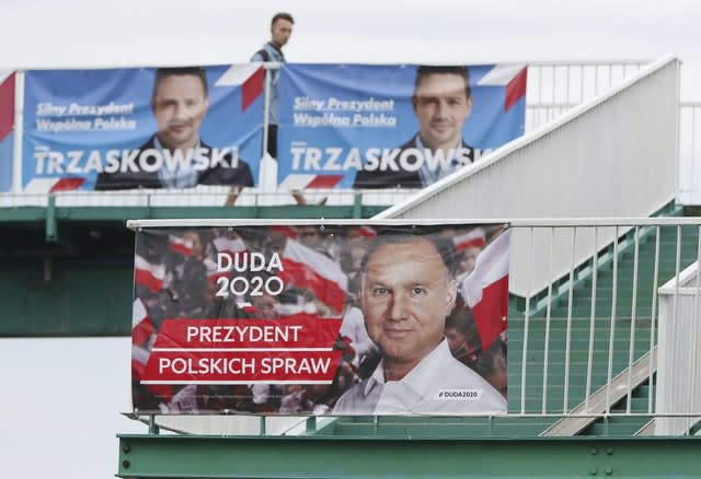 A man walks past campaign posters showing the two contenders in Poland's presidential election run-off (Czarek Sokolowski/AP)