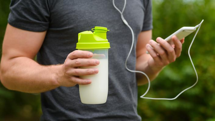 Nutritious protein cocktail in special shaker with a lot of milk for quenching the thirst and for taking a lot of useful vitamines. Male hand holds a smarthpone with headphones.