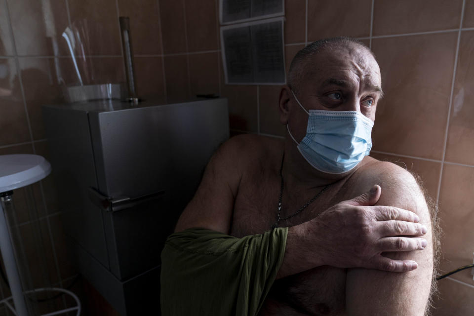 A Ukrainian serviceman gets ready to receive a dose of the AstraZeneca COVID-19 vaccine marketed under the name CoviShield at a military base in Kramatorsk, Ukraine, Tuesday, March 2, 2021. Ukraine plans to vaccinate 14.4 million people this year, or about 35% of its 41 million people. (AP Photo/Evgeniy Maloletka)