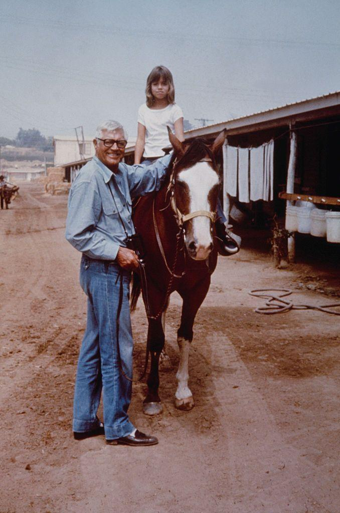 <p>Cary Grant stands next to his daughter Jennifer—his only child with ex-wife Dyan Cannon—as she rides a horse in 1976. </p>