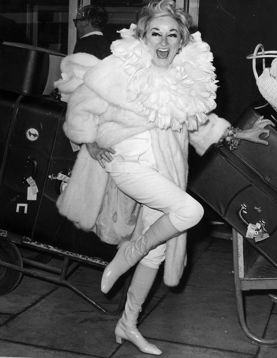 <p><strong>Phyllis Diller, 1968</strong><strong>:</strong> When this photo was taken, American comedian Phyllis Diller had just arrived at London's Heathrow airport with THIRTY-FIVE suitcases. Which is perhaps why she's wearing an absurd amount of fabric around her neck...so she doesn't have to check a 36th bag? </p>