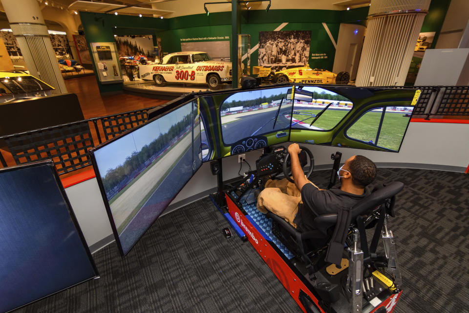 """In this image provided by the The Henry Ford, a person tries the auto racing simulator, part of the Driven To Win exhibit at the The Henry Ford Museum in Dearborn, Mich. The """"Driven to Win"""" exhibit took more than a decade from concept to its opening earlier this year. (Wes Duenkel/The Henry Ford via AP)"""