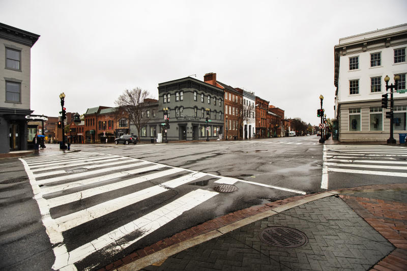 The streets in the shopping district of Georgetown are nearly empty Wednesday, March 25, 2020, in Washington. Streets are almost empty in usually crowded and busy shopping areas of the capital as Washington residents are urged to stay home to contain the spread of the coronavirus. (AP Photo/Manuel Balce Ceneta)