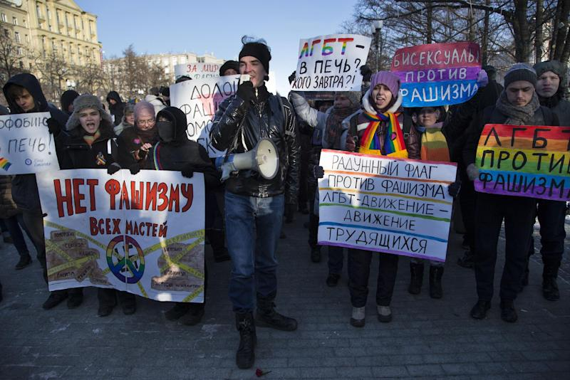 """FILE - In this Sunday, Jan. 19, 2014 file photo Russian gay rights activists march along a Moscow boulevard in downtown. Slogans read: ' Down with all Kinds of Fascism', ' Homophobia into the Fire!', ' For Peace without Racism ! ', and 'Bisexuals Against Fascism'. When the Sochi Winter Olympics begin on Friday, Feb. 7, 2014, many will be watching to see whether Russia will enforce its law banning gay """"propaganda"""" among minors if athletes, fans or activists wave rainbow flags or speak out in protest. The message so far has been confusing. (AP Photo/ Alexander Zemlianichenko)"""