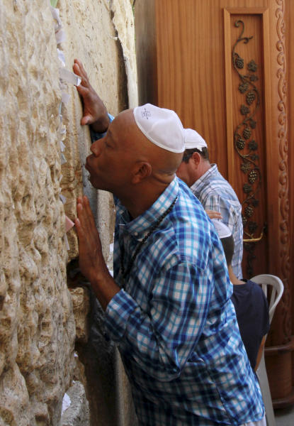 Hip hop mogul Russell Simmons kisses the stones of the Western Wall, the holiest site where Jews can pray, in Jerusalem's Old City, Thursday, June 21, 2012. The cofounder of the pioneering Def Jam Recordings record label, which has represented such artists like the Beastie Boys, Jay-Z, Lady Gaga, Jennifer Lopez, LL Cool J and Kanye West, is in Israel on the invitation of Israeli President Shimon Peres.(AP Photo/Blake Sobczak)