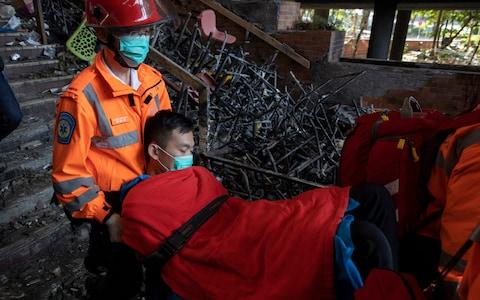 A man is evacuated by medics past charred debris from the Polytechnic University in Hong Kong on Wednesday, Nov. 20, 2019 - Credit: AP