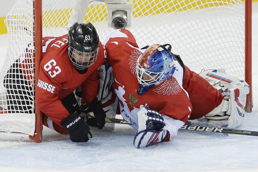Anja Stiefel of Switzerland and Goalkeeper Anna Prugova of Russia slide into the net during the 2014 Winter Olympics women's ice hockey quarterfinal game at Shayba Arena, Saturday, Feb. 15, 2014, in Sochi, Russia. (AP Photo/Matt Slocum)
