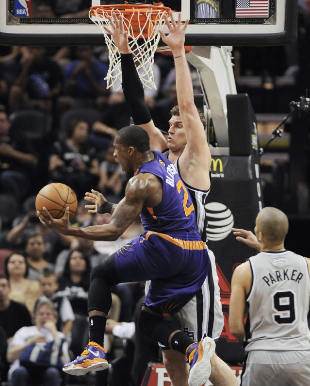 Phoenix Suns guard Eric Bledsoe, front, shoots against San Antonio Spurs forward Tiago Splitter, of Brazil, as Spurs' Tony Parker, right, of France, looks on, during the first half of an NBA basketball game on Friday, April 11, 2014, in San Antonio. (AP Photo/Darren Abate)