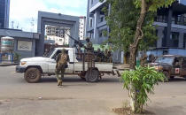 In this image made from video, unidentified soldiers patrol in a vehicle near the office of the president in the capital Conakry, Guinea Sunday, Sept. 5, 2021. Guinea's new military leaders sought to tighten their grip on power after overthrowing President Alpha Conde, warning local officials that refusing to appear at a meeting convened Monday would be considered an act of rebellion against the junta. (AP Photo)
