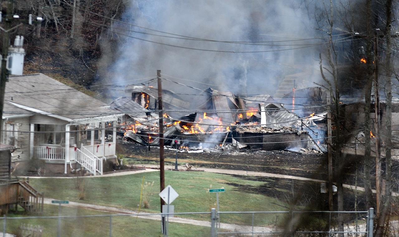 The remains of a residential structure is leveled and burning after a natural gas line explosion Tuesday afternoon Dec. 11, 2012 along Route 21 in between Sissonville, W.V. and Pocatalico, W.V. At least five homes went up in flames Tuesday afternoon and a badly burned section of the expressway in West Virginia was closed after a natural gas line exploded in an hour-long inferno. (AP Photo/The Daily Mail, Rober M. Wojcieszak ) MBO (REV-SHARE)