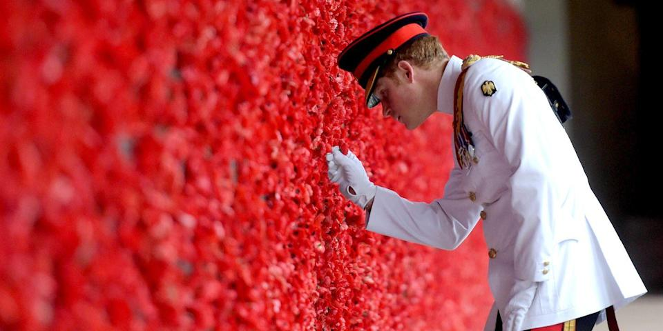<p>The prince places a poppy at the Roll of Honour during a visit to the Australian War Memorial. </p>